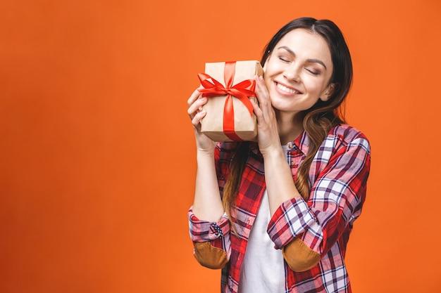 웃는 젊은 여자의 스튜디오 초상화 빨간색 선물 상자를 보유하고있다. 오렌지 배경에 대해 격리.