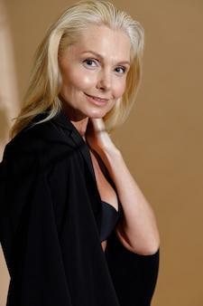 笑顔の上に下着と古典的な黒のジャケットでスタイリッシュな成熟したブロンドの女性のスタジオポートレート