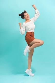 Студийный портрет удивленной позитивной девушки танцует