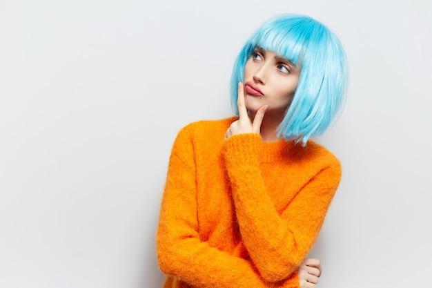 흰색 배경 복사 공간에 대해 턱 아래 손을 잡고 사려 깊은 어린 소녀의 스튜디오 초상화. 주황색 스웨터와 파란색 가발을 착용.