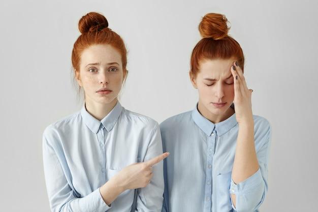 屋内でポーズをとって似ている2つの赤毛の姉妹のスタジオポートレート