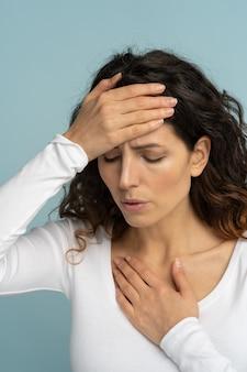 暑い夏の天候で熱射病を受けた女性のスタジオポートレート、彼女の額に触れ、孤立
