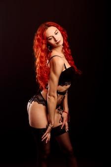 속옷에 빨간 머리 긴 곱슬 머리를 가진 젊은 매력적인 여자 모델의 스튜디오 초상화.