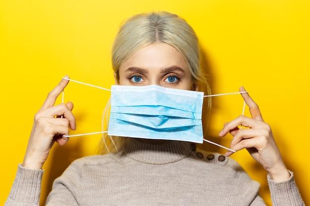 黄色の背景に、顔に医療インフルエンザマスクを保持している若いブロンドの女の子のスタジオの肖像画。