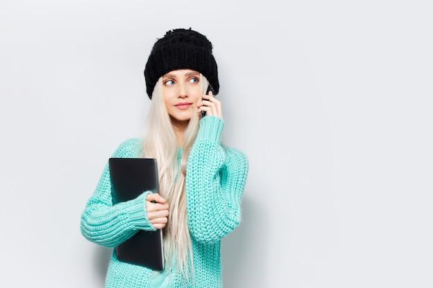 Студийный портрет молодой блондинки, держащей ноутбук, используя смартфон, в черной шляпе и синем свитере на белом фоне.