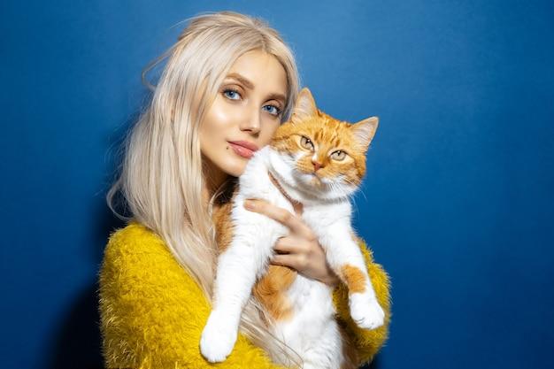 彼女の手で赤白猫を保持している若いブロンドの女の子のスタジオポートレート。青い色の背景。