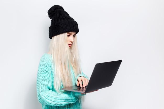 흰색 바탕에 노트북을 사용하는 젊은 금발 소녀의 스튜디오 초상화. 검은 모자와 청록색 스웨터를 입고.