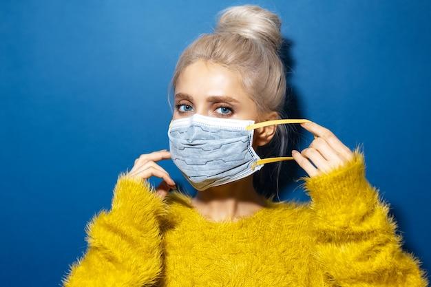 노란 스웨터를 입고 코로나 바이러스에 대 한 의료 얼굴 마스크를 씌우고 파란 눈을 가진 젊은 금발 소녀의 스튜디오 초상화. 팬텀 블루 색상의 배경입니다.