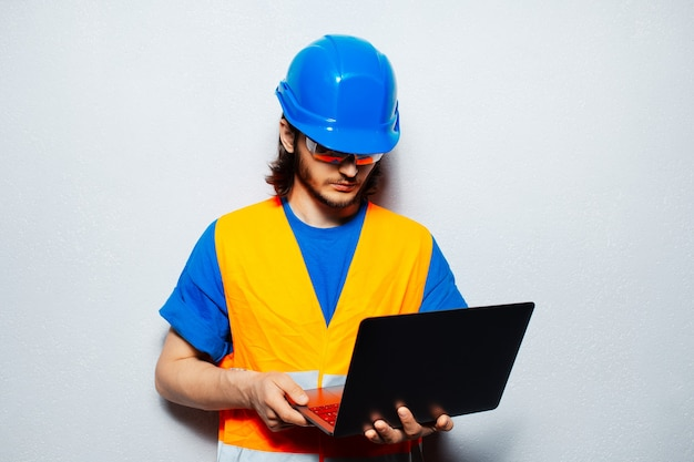 灰色の壁の背景にラップトップを使用して、安全装置を身に着けている若い建設労働者エンジニアのスタジオポートレート。