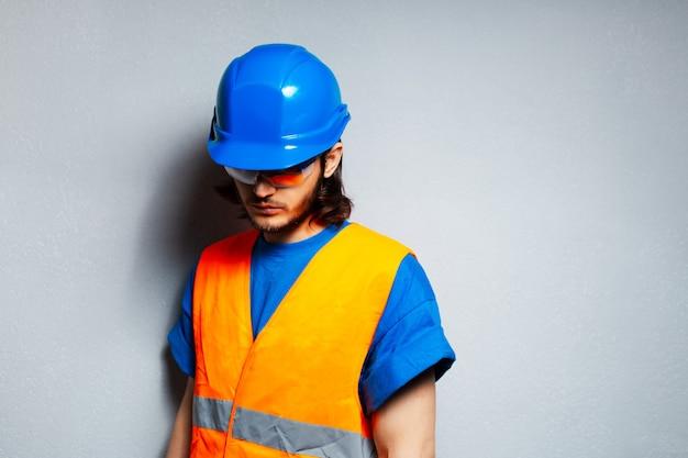 安全装置を身に着けている若い建設労働者エンジニアのスタジオポートレート。