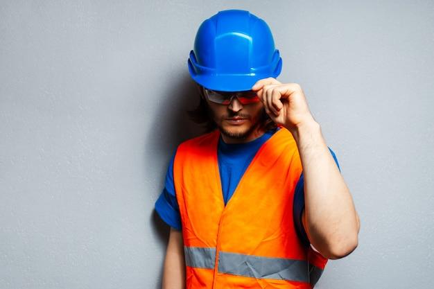 安全装置を身に着けている若い建設労働者のスタジオポートレート。