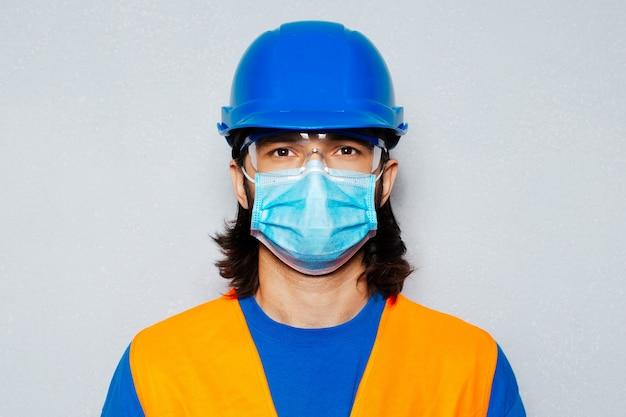 コロナウイルスとcovid-19に対する医療マスクを持つ若い建設労働者のスタジオポートレート