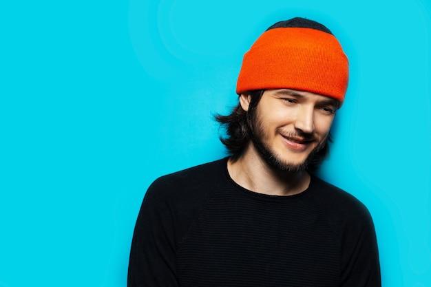 青い色の背景に若いクールな男のスタジオポートレート。