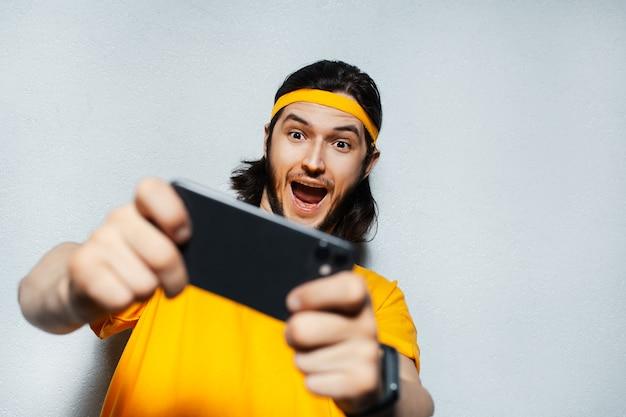 頭とシャツに黄色の帯を身に着けている灰色のテクスチャ背景にスマートフォンを使用して若い興奮した男のスタジオポートレート。