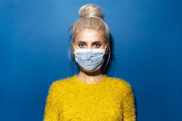 파란색의 질감 배경에 코로나 바이러스와 노란색 스웨터에 대한 의료 얼굴 마스크를 쓰고 금발 머리 롤빵, 젊은 여자의 스튜디오 초상화.