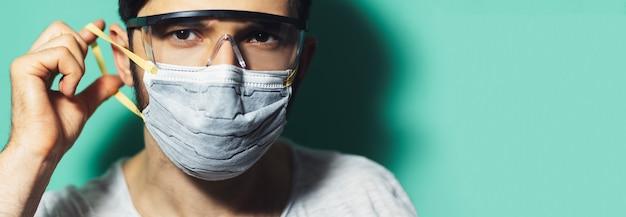 복사 붙여 넣기와 아쿠아 menthe 색상의 배경에 코로나 바이러스에 대한 안전 고글을 착용 의료 얼굴 마스크를 씌우고 젊은 남자의 스튜디오 초상화.