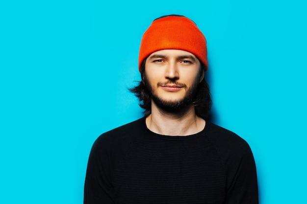 青い背景にオレンジ色の帽子と黒のセーターを着ている若いハンサムな男のスタジオの肖像画。