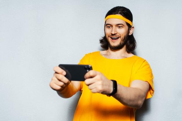 頭とシャツに黄色の帯を身に着けている灰色のテクスチャ背景にスマートフォンを使用して若い幸せな男のスタジオの肖像画。