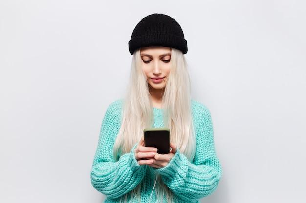 흰색 바탕에 스마트 폰을 사용 하여 젊은 hipster 금발 소녀의 스튜디오 초상화. 검은 비니 모자와 파란색 스웨터를 입고.