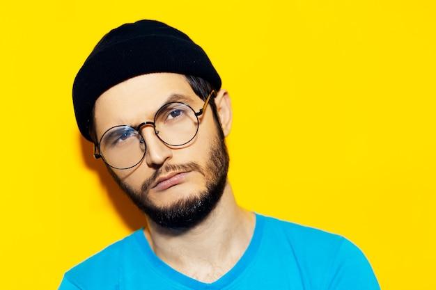 노란색의 배경에 검은 비니 모자와 둥근 안경을 착용하는 젊은 hipster 남자의 스튜디오 초상화.