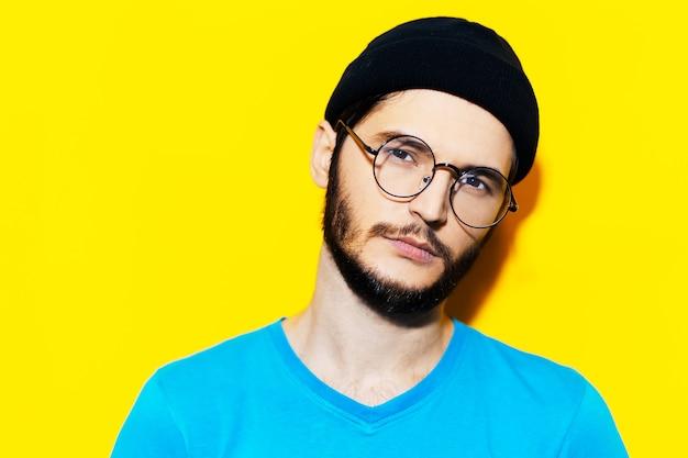 黄色の背景に丸い眼鏡、青いシャツ、帽子を身に着けている若いヒップスターのスタジオポートレート。
