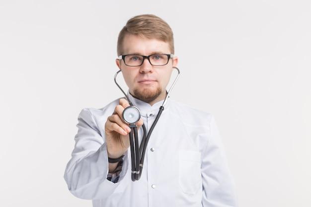 안경을 쓰고 청진기를 가진 젊은 남성 의사의 스튜디오 초상화