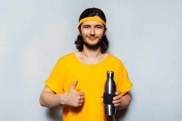 頭とシャツに黄色の帯を身に着けている灰色のテクスチャ壁の背景に親指を表示し、鋼のサーモウォーターボトルを保持している若い男のスタジオの肖像画。