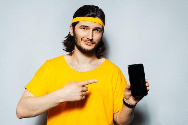 頭とシャツに黄色の帯を身に着けている灰色のテクスチャ背景にスマートフォンで指を示す若い男のスタジオポートレート。