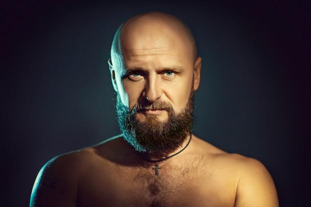 暗闇の中でひげを持つ若者のスタジオポートレート