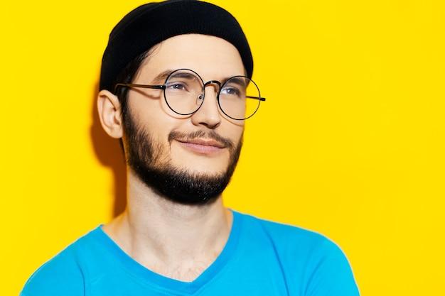 黄色の背景に黒のビーニー帽子、丸い眼鏡、シアンのシャツを着た若いミレニアル世代のスタジオポートレート。
