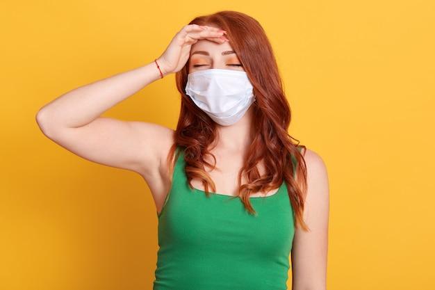 닫힌 된 눈을 가진 젊은 redhaired 여자의 스튜디오 초상화, 두통, 이마에 손을 유지, 노란색 배경에 의료 독감 마스크와 녹색 티셔츠를 입고.