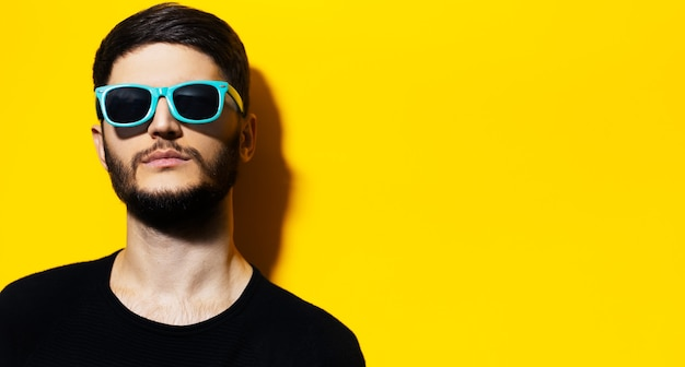 コピースペースと黄色の背景にシアンのサングラスを身に着けている若い深刻な自信を持っている男のスタジオポートレート。