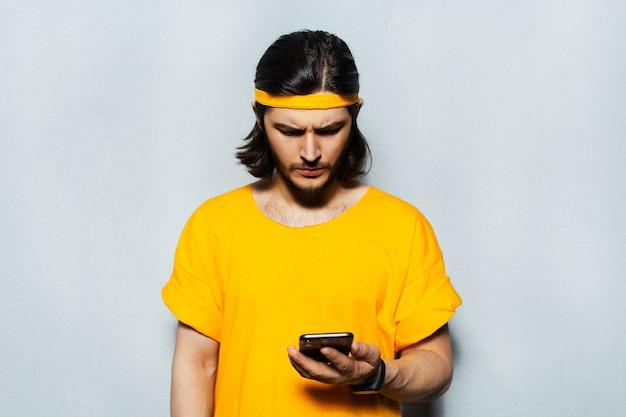 頭とシャツに黄色の帯を身に着けている灰色のテクスチャ背景にスマートフォンで見ている若い真面目な男のスタジオの肖像画。