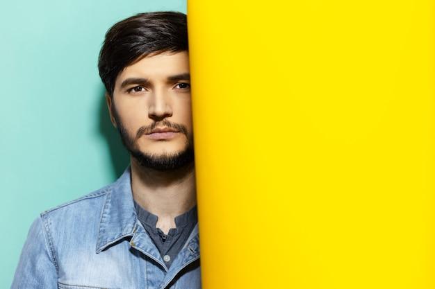 데님 재킷에 젊은 심각한 사려 깊은 남자의 스튜디오 초상화, 노란색과 아쿠아 menthe 색상의 두 배경 사이에 서.