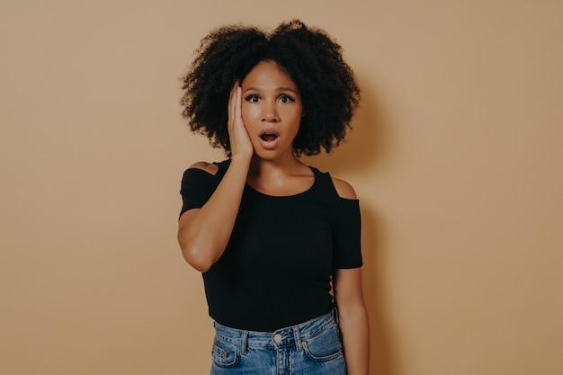 나쁜 소식을 듣고 예상치 못한 표정을 짓고 충격을 받은 젊은 아프리카 여성의 스튜디오 초상화, 혼혈 여성은 턱을 낮추고 캐주얼 복장을 하고 베이지색 벽에 포즈를 취했습니다.