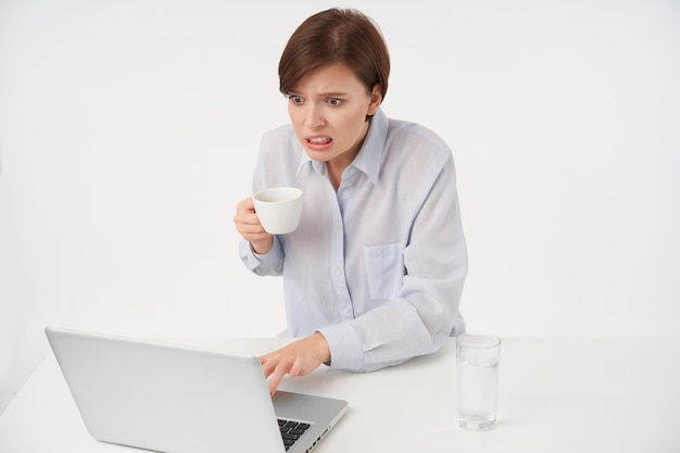 混乱した顔で不快なメッセージを読み、上げられた手でコーヒーを保持し、白で隔離の自然なメイクで若い短い髪の女性のスタジオの肖像画