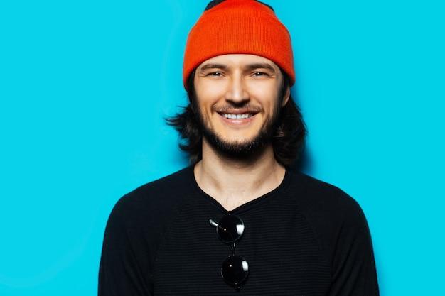 青い背景に黒いセーターとオレンジ色の帽子の若い笑顔の男のスタジオの肖像画。