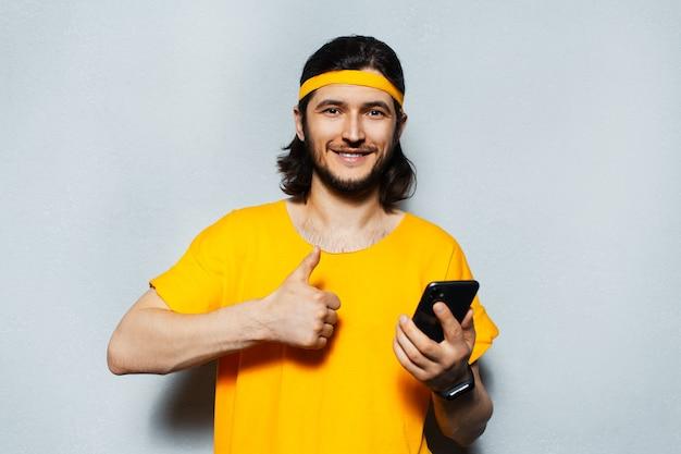 頭とシャツに黄色の帯を身に着けている灰色のテクスチャ背景にスマートフォンを手に親指を表示している若い笑顔の男のスタジオの肖像画。