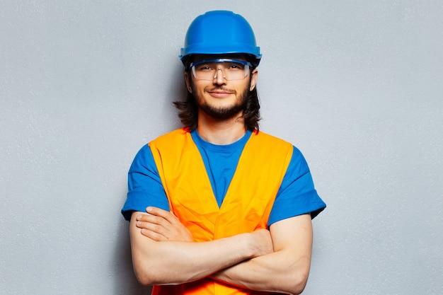 腕を組んで、安全装置を身に着けている建設労働者エンジニアの若い笑顔の男のスタジオの肖像画