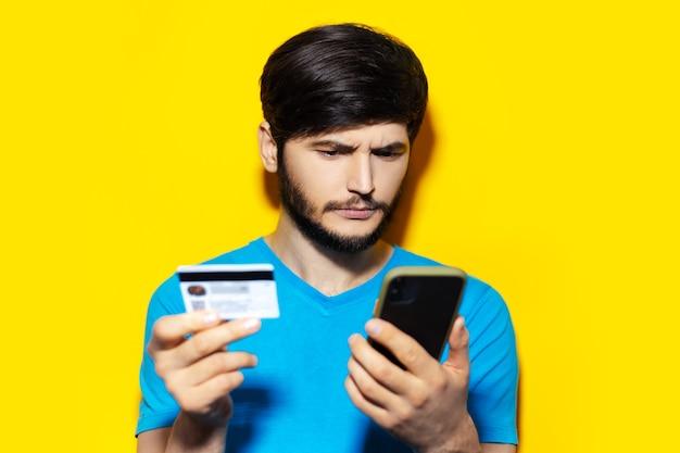 黄色の背景にスマートフォンとクレジットカードを使用して若い思いやりのある男のスタジオポートレート。