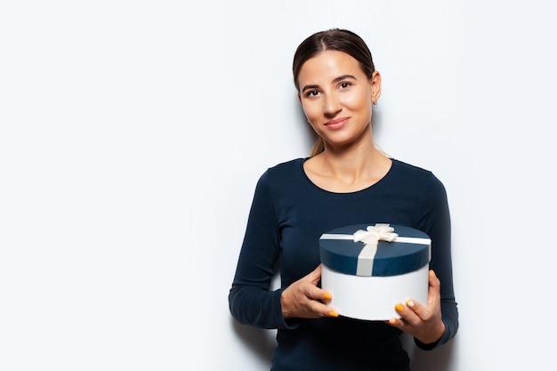 선물 상자를 들고 젊은 여자의 스튜디오 초상화