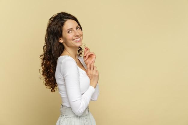 Студийный портрет молодой женщины с чистой свежей кожей, счастливая зубастая улыбка, здоровые естественные вьющиеся волосы