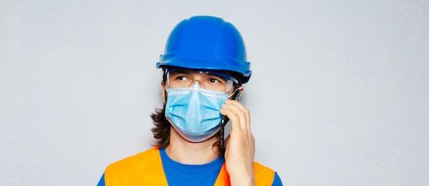 スマートフォンで話し、コロナウイルスまたはcovid-19に対する医療用フェイスマスクを着用し、灰色の背景に安全建設機械を身に着けている若い労働者エンジニアのスタジオポートレート。