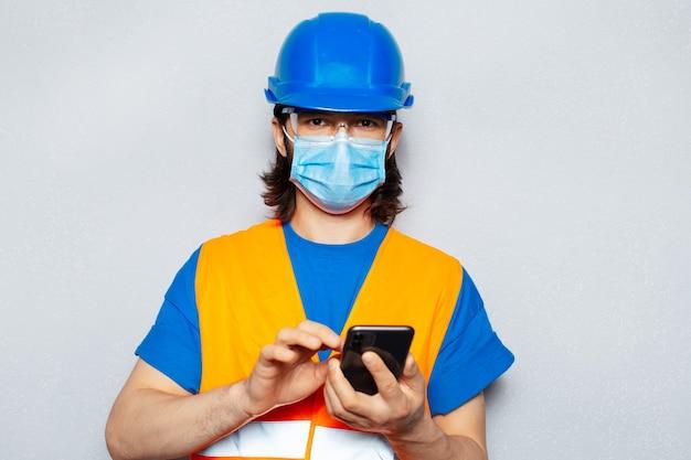 スマートフォンを使用して、コロナウイルスまたはcovid-19に対して医療用フェイスマスクを着用している若い労働者エンジニアのスタジオポートレート