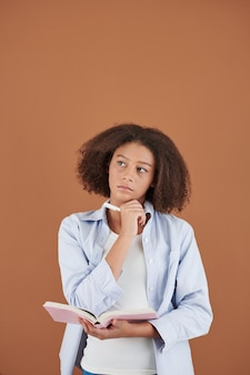 Studio portrait of pensive teenage girl taking notes in her diary or planner