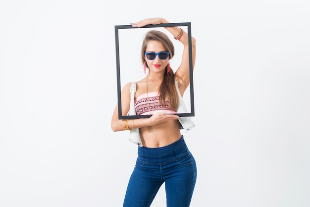 Studio portrait of a playful girl having fun, wearing sunglasses and trendy summer outfit.