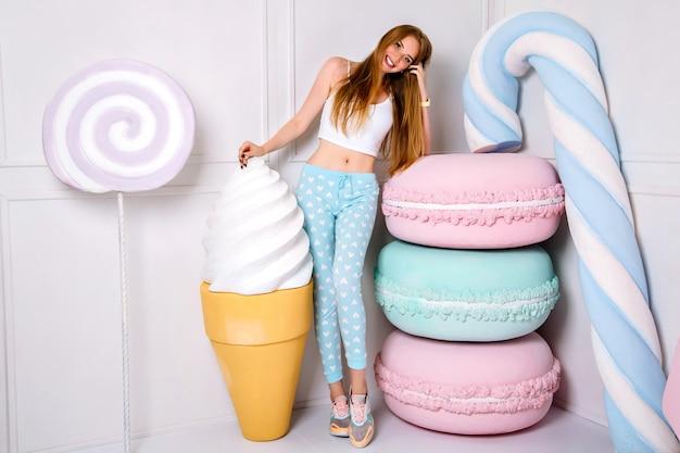 Studio portrait of pretty blonde woman wearing cute pijama and posing near huge sweets