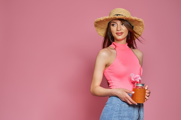 Studio portrait of pretty cute adorable gorgeous lady holding glass of juice in hand wearing straw h...