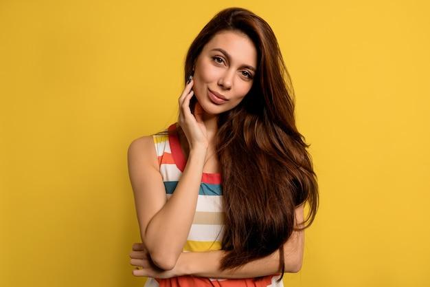 Ritratto in studio di bella signora con lunghi capelli scuri che indossa abiti estivi luminosi in posa con emozioni felici sul muro giallo