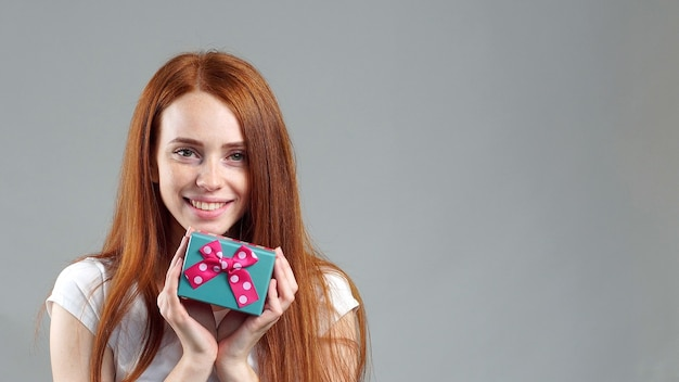 Studio portrait of a pretty redhead girl holding a small gift box